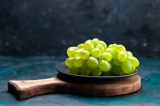 Vooraanzicht verse groene druiven zacht sappig fruit binnen plaat op donkerblauw bureau.