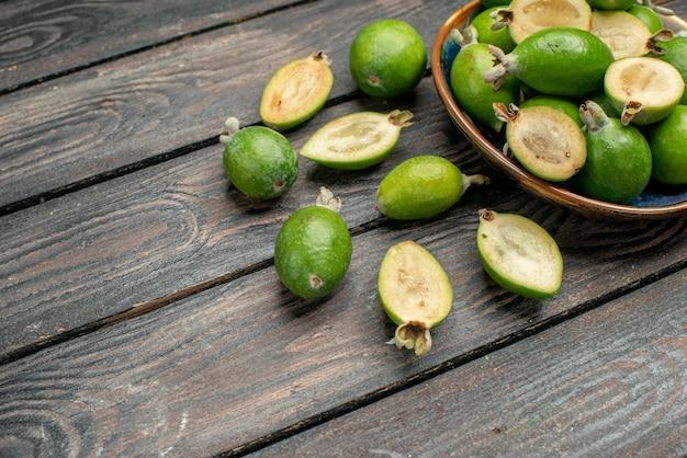 Vooraanzicht verse groene feijoas binnen plaat op een houten rustiek bureau fruit kleurenfoto sap rijp zuur