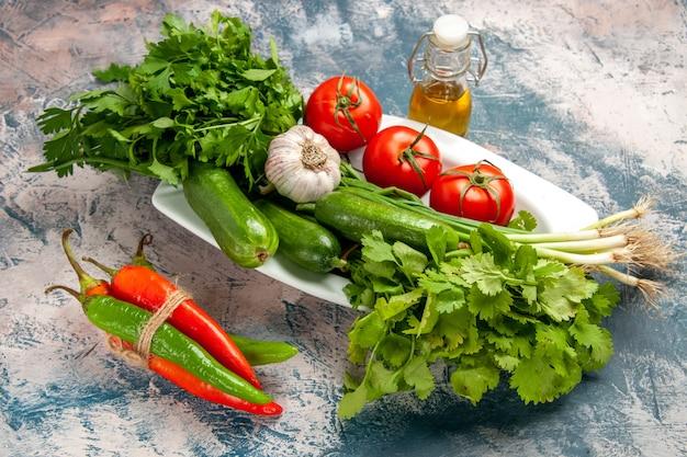 Vooraanzicht verse groene ui met tomaten en greens op lichtblauwe achtergrondkleur foto rijpe maaltijdsalade