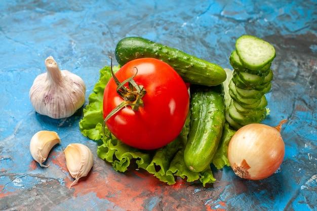 Vooraanzicht verse groenten komkommer tomaat groene salade en knoflook op een blauwe achtergrond maaltijdsalade gezondheid rijp voedsel dieet kleur