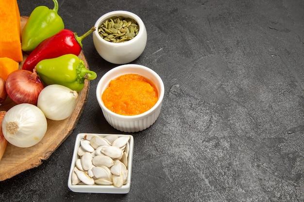 Vooraanzicht verse groenten met gesneden pompoen op grijze achtergrond rijpe salade kleur vers