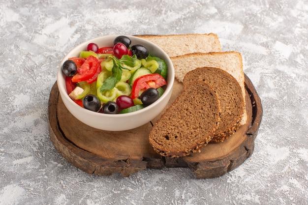 Vooraanzicht verse groentesalade met gesneden komkommers, tomaten, olijven en witte kaas binnen plaat met brood op de grijze maaltijd van de de salade van het bureau plantaardige voedsel