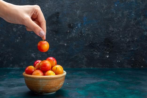 Vooraanzicht verse kersen-pruimen zacht en zuur fruit in kleine pot op donkerblauw bureau fruit vers zacht rijp
