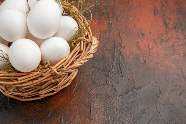 Vooraanzicht verse kippeneieren in de mand op het donkere oppervlak