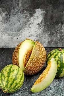 Vooraanzicht verse meloen met watermeloen op de donker-lichte achtergrond