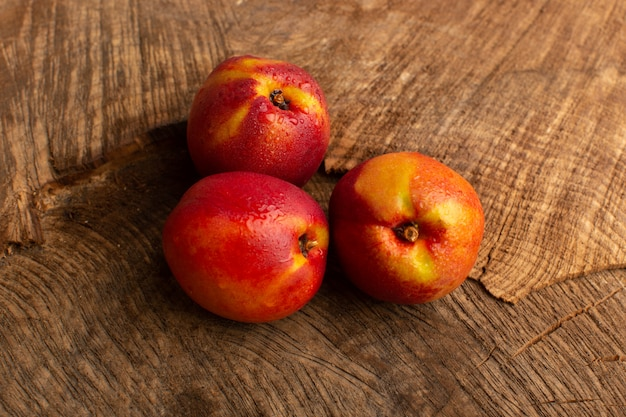 Vooraanzicht verse perziken oranje gekleurd op houten bureau