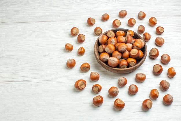 Vooraanzicht verse rauwe hazelnoten op witte bureaunoot snack film plant voedsel walnoot