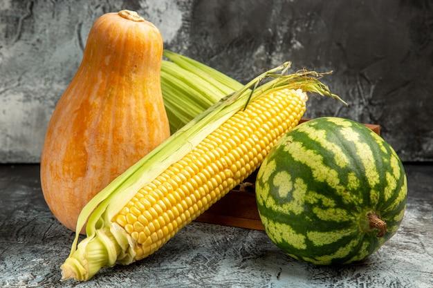 Vooraanzicht verse rauwe maïs met meloen en watermeloen op donker-lichte achtergrond