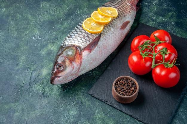 Vooraanzicht verse rauwe vis met schijfjes citroen en tomaten op donkerblauw oppervlak haai zeevruchten maaltijd oceaan horizontaal water vlees diner eten