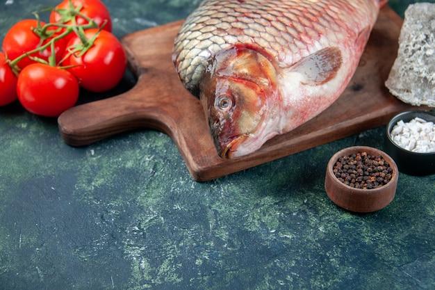 Vooraanzicht verse rauwe vis op snijplank met tomaten donkerblauw oppervlak vlees water oceaan voedsel omega kleur maaltijd zeevruchten horizontaal