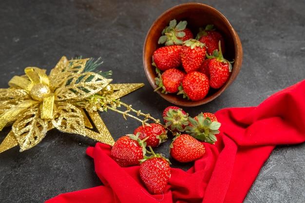 Vooraanzicht verse rode aardbeien in plaat met speelgoed op donkere achtergrondfoto kleur veel fruit zacht