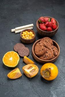 Vooraanzicht verse rode aardbeien met koekjes op donkere achtergrond