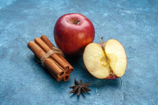 Vooraanzicht verse rode appels met kaneel op blauwe ondergrond