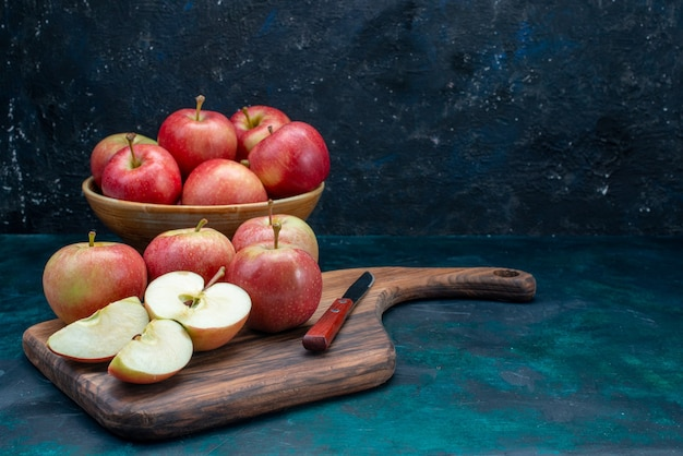 Vooraanzicht verse rode appels sappig en zacht binnen plaat op het donkerblauwe bureau fruit verse rijpe zachte vitamine