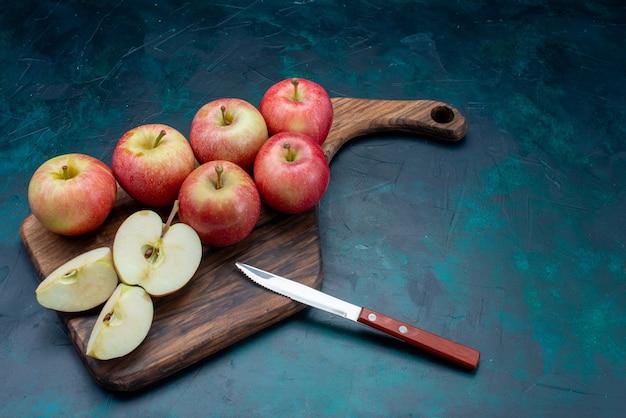 Vooraanzicht verse rode appels sappig en zacht met bruin bureau op de donkerblauwe achtergrondfruit verse rijpe zachte vitamine