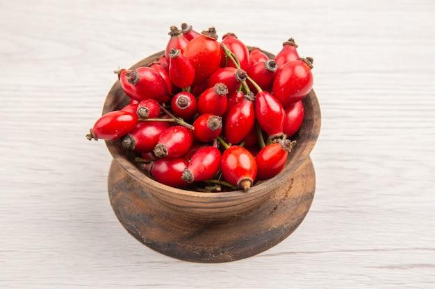 Vooraanzicht verse rode bessen in kleine plaat op witte achtergrond gezondheid berry wilde kleur fruit foto