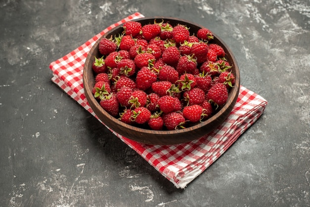 Vooraanzicht verse rode frambozen binnen plaat op grijze fruitbes kleur cranberry wilde foto