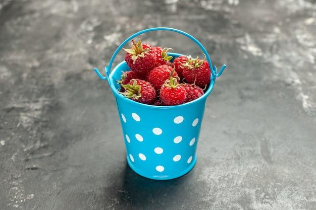 Vooraanzicht verse rode frambozen in kleine mand op grijze fruitkleur cranberry wilde fotobes