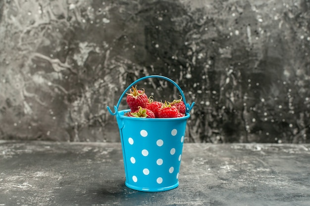 Vooraanzicht verse rode frambozen in kleine mand op grijze vruchten kleur cranberry wilde foto berry