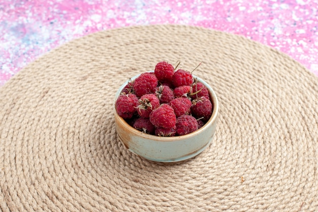 Vooraanzicht verse rode frambozen in kleine pot op de roze achtergrond.