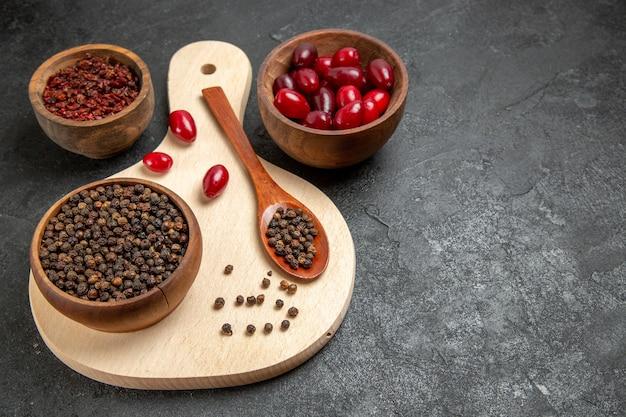 Vooraanzicht verse rode kornoeljes met kruiden op donkergrijs bureau
