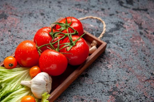 Vooraanzicht verse rode tomaten met knoflook en groene salade in houten bord op blauwe achtergrond