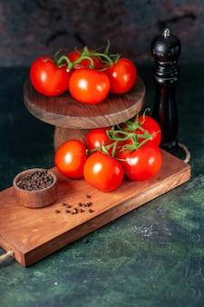 Vooraanzicht verse rode tomaten op donkere achtergrond