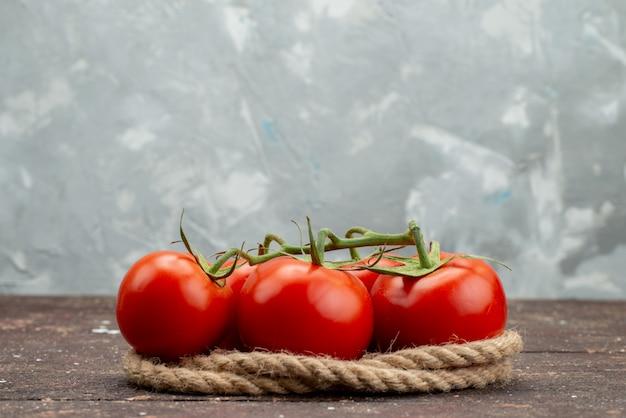 Vooraanzicht verse rode tomaten rijp en geheel op wit, met touwen plantaardige fruit bessen voedsel kleur