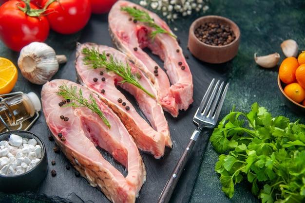 Vooraanzicht verse vis plakjes met rode tomaten en greens op donkere ondergrond zeevruchten salade maaltijd oceaan rauw vlees water foto diner kleur