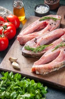 Vooraanzicht verse vis plakjes met tomaten en greens op donkere ondergrond voedsel gezondheid peper kleur maaltijd salade zeevruchten oceaan water vis dieet