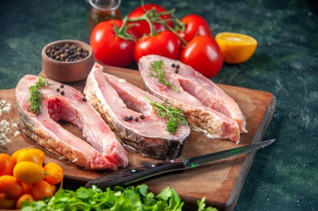 Vooraanzicht verse vis plakjes met tomaten en greens op donkere ondergrond voedsel gezondheid vis peper kleur maaltijd zeevruchten oceaan water dieet salade