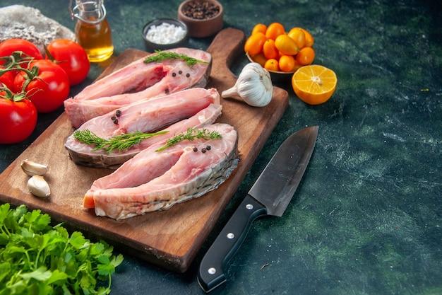 Vooraanzicht verse vis plakjes met tomaten op donkerblauw oppervlak voedsel gezondheid peper kleur maaltijd salade zeevruchten oceaan water vis dieet