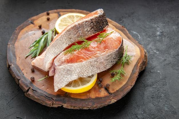 Vooraanzicht verse visschijfjes met schijfjes citroen op donkere schotel kleur voedsel vlees zeevruchten foto rauw
