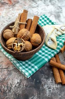 Vooraanzicht verse walnoten met kaneel en zoet gebak op lichte ondergrond