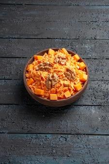 Vooraanzicht verse wortelsalade geraspte salade met walnoten en knoflook op de donkere bureaudieet rijpe salade gezondheidskleur