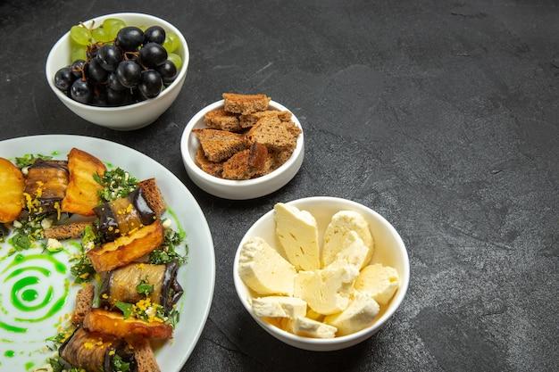 Vooraanzicht verse zachte druiven met witte kaas aubergine broodjes en gesneden brood op donkere achtergrond maaltijd eten schotel melk fruit