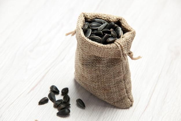 Vooraanzicht verse zonnebloempitten zwart gekleurde zaden in kleine zak op witte achtergrond zaad snack foto veel olie