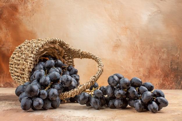 Vooraanzicht verse zwarte druiven in mand op de lichte achtergrond rijp fruit wijn zachte foto