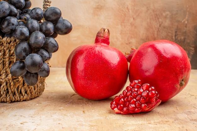 Vooraanzicht verse zwarte druiven met granaatappels op de lichte achtergrond rijp fruit wijn zachte foto