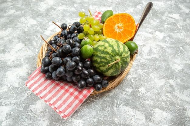 Vooraanzicht verse zwarte druiven met sinaasappel en feijoa op witte achtergrond fruit zacht rijp vers