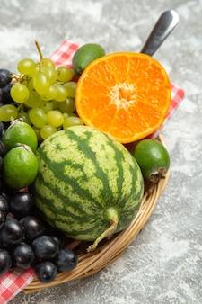 Vooraanzicht verse zwarte druiven met sinaasappel en feijoa op witte achtergrond rijp fruit, zachte verse vitamineboom