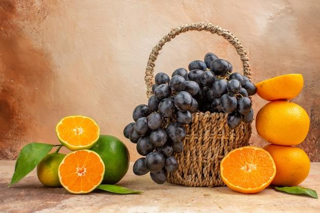 Vooraanzicht verse zwarte druiven met sinaasappel op lichte achtergrond zachte foto rijpe vruchten vitamineboom