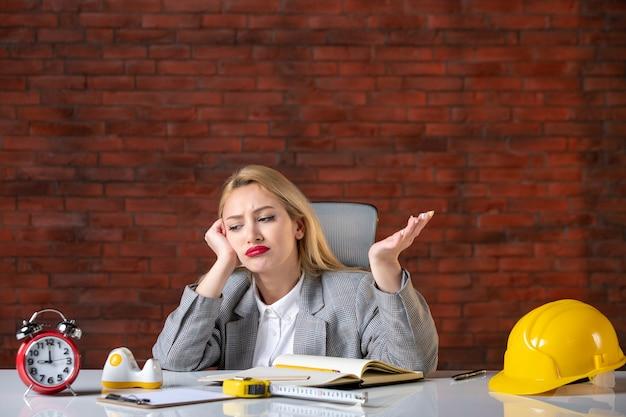 Vooraanzicht verveeld vrouwelijke ingenieur achter haar werkplek