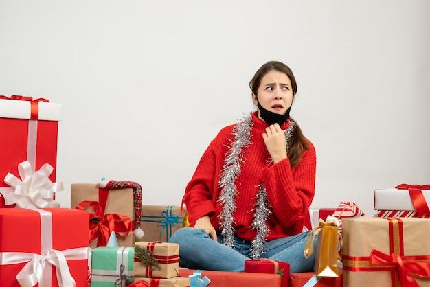 Vooraanzicht verward meisje met rode trui opstijgen van haar masker rond zittend cadeautjes