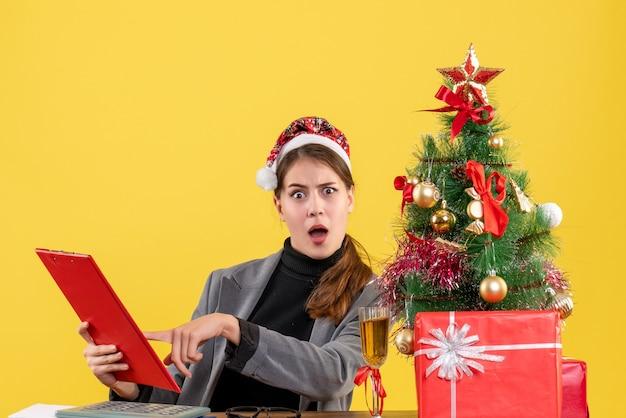 Vooraanzicht verward meisje met xmas hoed zittend aan de tafel documentenmap kerstboom en geschenken cocktail op tafel gele achtergrond