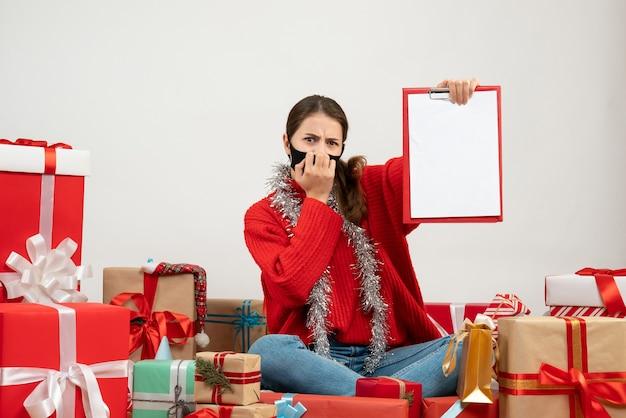 Vooraanzicht verward meisje met zwart masker met documenten die rondhangen cadeautjes