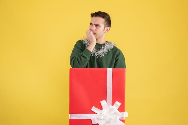 Vooraanzicht verwarde jonge man achter grote geschenkdoos op geel