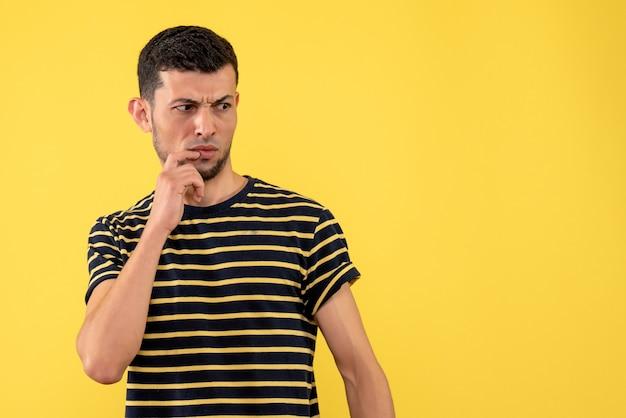 Vooraanzicht verwarde jonge man in zwart-wit gestreepte t-shirt gele geïsoleerde achtergrond kopie plaats
