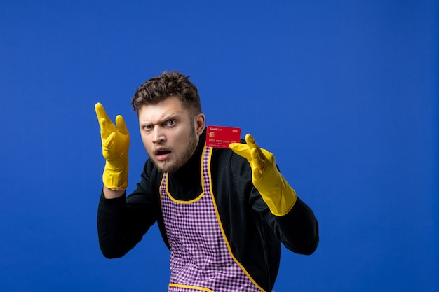 Vooraanzicht verwarde jonge man met creditcard in linkerhand op blauwe ruimte