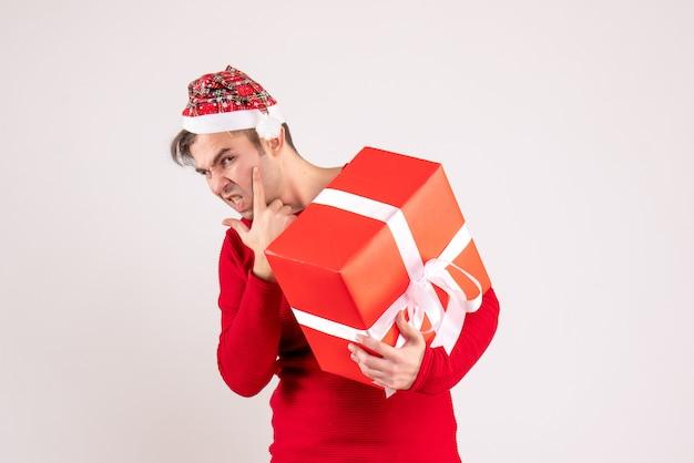Vooraanzicht verwarde jonge man met kerstmuts staande op wit